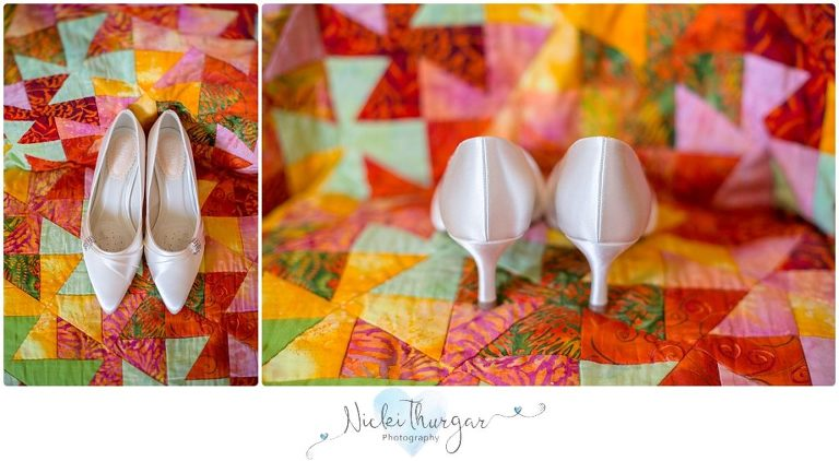 white wedding shoes on colourful quilt